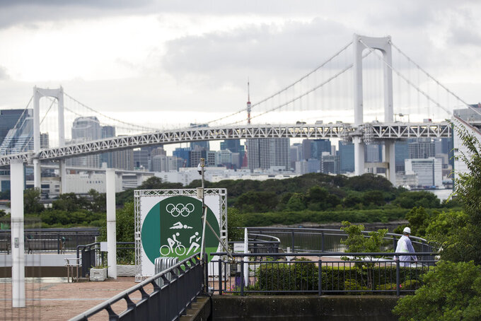 A guard, lower right, walks around a park being prepared for the Olympics and Paralympics Games in Tokyo on Thursday, July 1, 2021. (AP Photo/Hiro Komae)