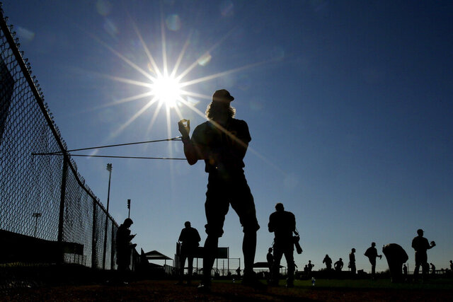 San Diego Padres pitcher Chris Paddack uses an elastic rope to stretch during baseball spring training Thursday, Feb. 13, 2020, in Peoria, Ariz. (AP Photo/Charlie Riedel)