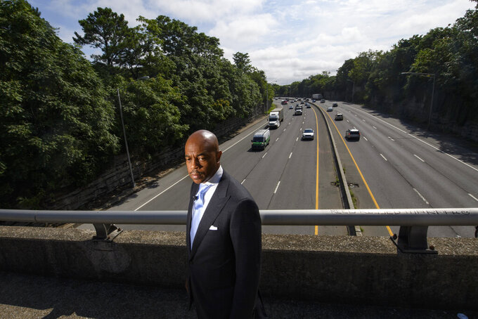 Tennessee State Rep. Harold Love, Jr. stands on an overpass over I-40, Monday, July, 19, 2021, near the site of his family's former home on the north side of Nashville, Tenn. Love Jr.'s father, a Nashville city councilman, was forced to sell his home near here to make way for the highway, but put up a fight in the 1960s against the rerouting of Interstate 40 because he believed it would stifle and isolate Nashville's Black community. Love Jr. is now part of a group pushing to build a cap across the highway, behind him, that creates a community space to help reunify the city. (AP Photo/John Amis)