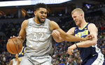 Minnesota Timberwolves' Karl-Anthony Towns, left, tries to keep Denver Nuggets' Mason Plumlee at bay during the first half of an NBA basketball game Wednesday, April 11, 2018, in Minneapolis. (AP Photo/Jim Mone)