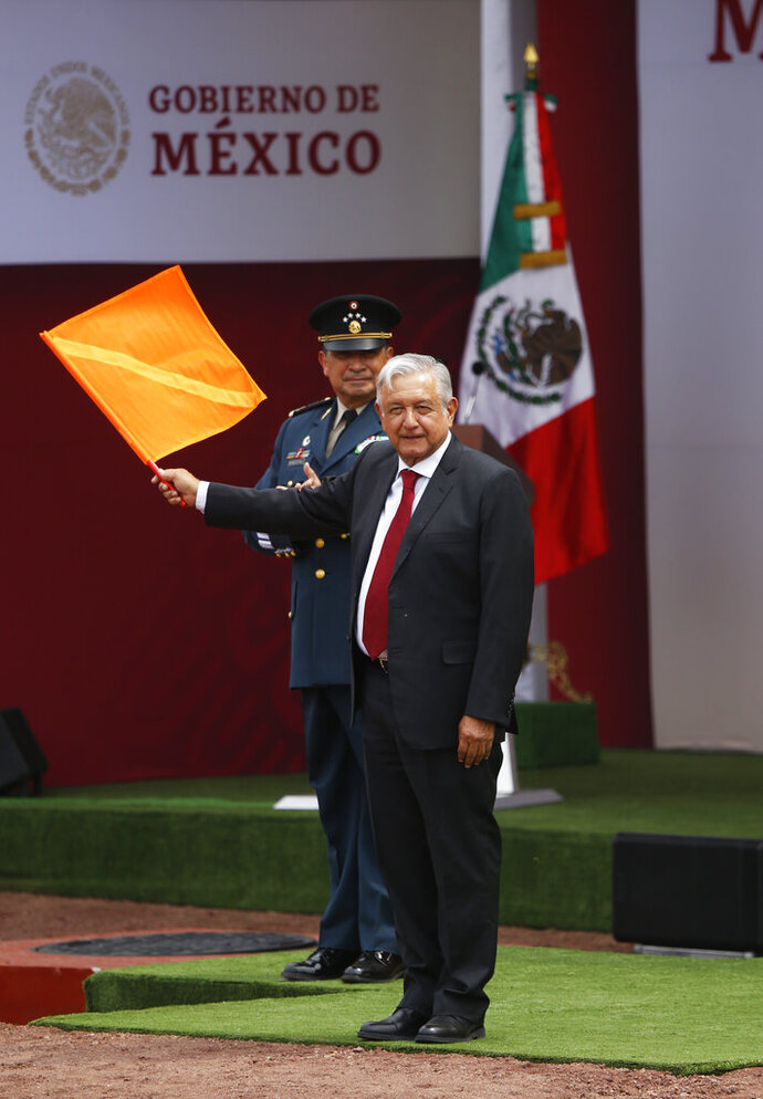 Mexican President Andrés Manuel López Obrador, waves a flag to launch construction work during a ceremony at the Military Airbase Number 1 in Santa Lucia, on the outskirts of Mexico City, Monday, April 29, 2019. López Obrador symbolically launched work on a new airport for Mexico City to replace the nearly half-built $13 billion project he cancelled upon taking office.(AP Photo/Marco Ugarte)
