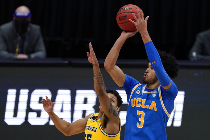 UCLA guard Johnny Juzang (3) shoots over Michigan guard Eli Brooks, left, during the first half of an Elite 8 game in the NCAA men's college basketball tournament at Lucas Oil Stadium, Tuesday, March 30, 2021, in Indianapolis. (AP Photo/Michael Conroy)
