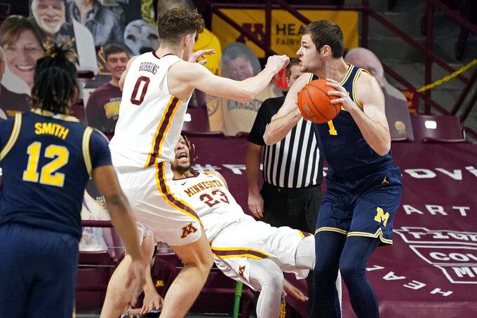 Minnesota's Brandon Johnson (23) falls as he defends against Michigan's Hunter Dickinson (1) during the first half an NCAA college basketball game, Saturday, Jan. 16, 2021, in Minneapolis. (AP Photo/Jim Mone)