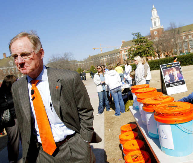 FILE - In this March 10, 2008 file photo, Oklahoma State University President Burns Hargis walks around campus in Stillwater, Okla. Oklahoma's two largest universities announced Tuesday, Oct. 6, 2020, that start of their spring semester will be delayed by one week and spring break is canceled because of the coronavirus pandemic.