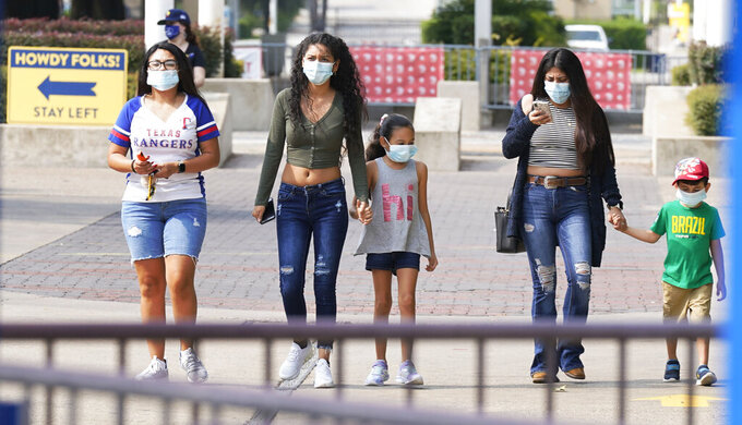 People wear masks as they walk the main concourse at Fair Park in Dallas on Sept. 19, 2020. The Texas and Oklahoma college football matchup will be a different game-day atmosphere this year with small crowds, no State Fair, a few food vendors, masks and social distancing. (AP Photo/LM Otero