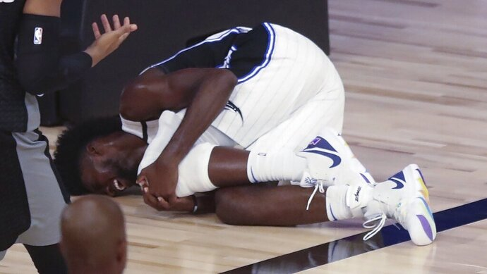 Orlando Magic forward Jonathan Isaac lies on the court holding his left knee after falling during a play in the fourth quarter against the Sacramento Kings in an NBA basketball game Sunday, Aug. 2, 2020, in Lake Buena Vista, Fla. (Charles King/Orlando Sentinel via AP)