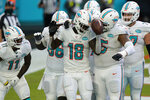 Miami Dolphins wide receiver Preston Williams (18) is congratulated by his teammates after scoring a touchdown, during the first half of an NFL football game against the New York Jets, Sunday, Oct. 18, 2020, in Miami Gardens, Fla. (AP Photo/Lynne Sladky)