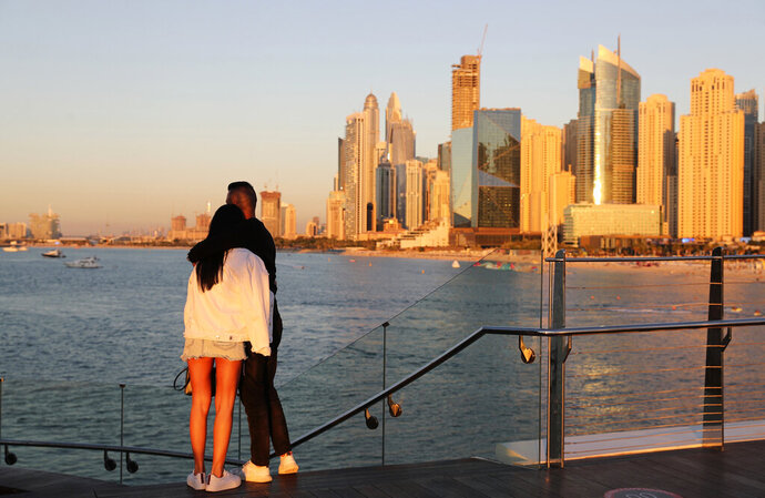 Tourists look at the skyline at sunset, in Dubai, United Arab Emirates, Tuesday, Jan. 12, 2021. Since becoming one of the world's first destinations to open up for tourism, Dubai has promoted itself as the ideal pandemic vacation spot. With peak tourism season in full swing, coronavirus infections are surging to unprecedented heights, with daily case counts nearly tripling in the past month, but in the face of a growing economic crisis, the city won't lock down and can't afford to stand still. (AP Photo/Kamran Jebreili)