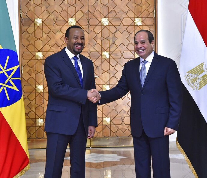 In this Sunday, June 10, 2018 photo, provided by Egypt's state news agency, MENA, Egyptian President Abdel-Fattah el-Sissi, right, shakes hands with Ethiopian Prime Minister Abiy Ahmed, in Cairo, Egypt. Egypt released 32 Ethiopian prisoners during a visit by the country's prime minister, in which he vowed that Ethiopia will not reduce Egypt's share of Nile waters, as his country works to complete what will be Africa's largest hydroelectric dam, officials said Monday. (MENA via AP)