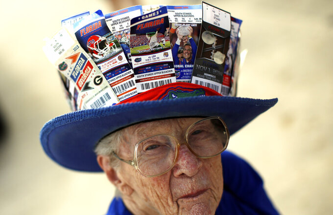 FILE - Florida fan Evelyn Stark, 86, wears a hat featuring all the ticket stubs since her first Florida-Georgia game in 1956, while tailgating with friends at an NCAA college football game between Florida and Georgia in Jacksonville, Fla., in this Saturday, Oct. 31, 2015, file photo. College football programs are transitioning from traditional paper tickets to digital ticketing. Many fans like the feel of holding a ticket in their hand and hanging on to them as keepsakes. Others welcome the convenience of having a barcode on their smartphone scanned at the gate. (AP Photo/Stephen B. Morton, File)