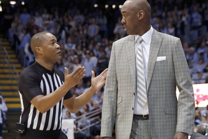 An official explains a call to Wake Forest head coach Danny Manning during the first half of an NCAA college basketball game in Chapel Hill, N.C., Tuesday, March 3, 2020. (AP Photo/Chris Seward)