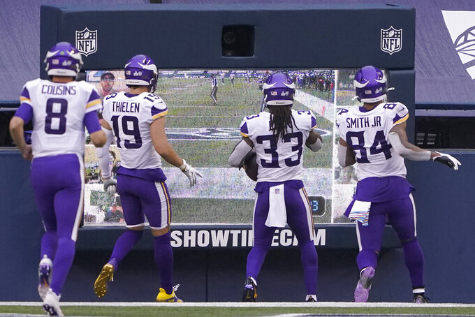 Minnesota Vikings' Dalvin Cook (33) heads to a monitor with teammates to celebrate after scoring against the Seattle Seahawks during the first half of an NFL football game, Sunday, Oct. 11, 2020, in Seattle. (AP Photo/Ted S. Warren)