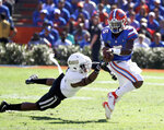 Florida quarterback Emory Jones, right, scrambles from the pocket as he tries to get past Idaho defensive back Tyrese Dedmon, left, during the first half of an NCAA college football game, Saturday, Nov. 17, 2018, in Gainesville, Fla. (AP Photo/John Raoux)