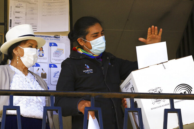 Accompanied by his mother, left, and wearing a mask to curb the spread of COVID-19, Yaku Perez, presidential candidate representing the Indigenous party Pachakutik, casts his ballot for president during general elections in Tarqui, Ecuador, Sunday, Feb. 7, 2021. (AP Photo/Marcelo Suquilanda)