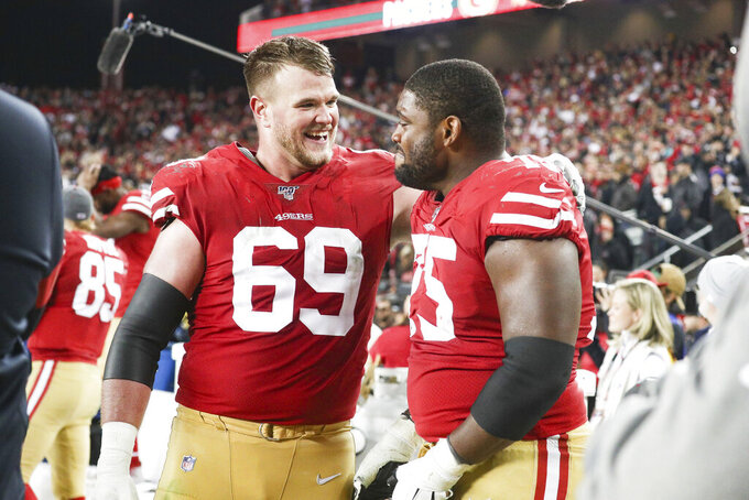 San Francisco 49ers offensive tackle Mike McGlinchey (69) comforts a tearful offensive guard Laken Tomlinson (75), who was overcome by emotion as the 49ers defeated the Green Bay Packers during the NFL NFC Championship football game, Sunday, Jan. 19, 2020 in Santa Clara, Calif. The 49ers defeated the Packers 37-20. (Margaret Bowles via AP)