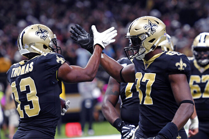New Orleans Saints wide receiver Michael Thomas (13) celebrates his touchdown reception with tight end Jared Cook (87) in the second half of an NFL football game in New Orleans, Sunday, Oct. 6, 2019. (AP Photo/Bill Feig)
