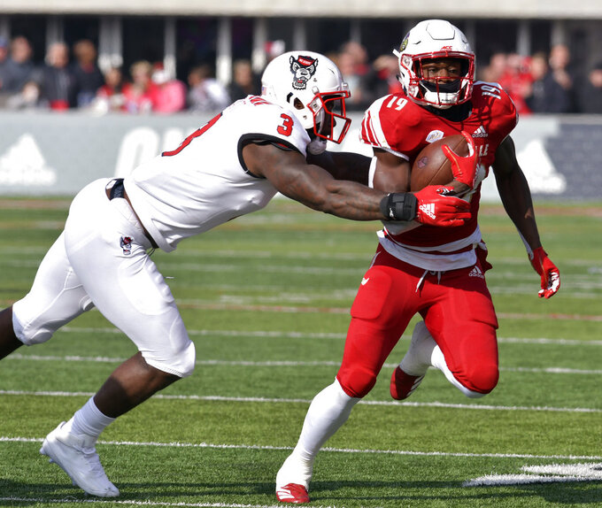 North Carolina State linebacker Germaine Pratt (3) attempts to tackle Louisville running back Hassan Hall (19) during the first half of an NCAA college football game, in Louisville, Ky., Saturday, Nov. 17, 2018. (AP Photo/Timothy D. Easley)