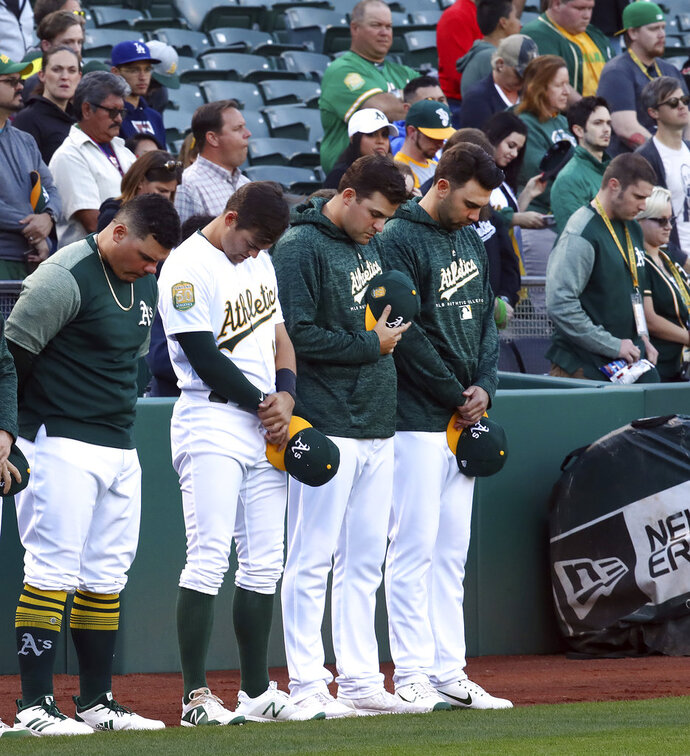 Oakland Athletics including Bruce Maxwell, left, bow their heads in memory of Gretchen Piscotty, mother of right fielder Stephen Piscotty, prior to a baseball game against the Houston Astros Monday, May 7, 2018, in Oakland, Calif. Gretchen Piscotty, 55, died yesterday in Pleasanton, Calif., less than a year after being diagnosed with amyotrophic lateral sclerosis (ALS), a neuromuscular disorder also known as Lou Gehrig's disease. (AP Photo/Ben Margot)