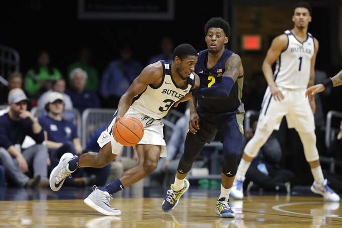 Butler's Kamar Baldwin (3) is defended by Marquette's Sacar Anim (2) during overtime of an NCAA college basketball game, Friday, Jan. 24, 2020, in Indianapolis. Butler won 89-85. (AP Photo/Darron Cummings)