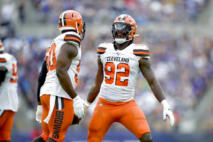 Cleveland Browns defensive end Chad Thomas (92) celebrates with defensive end Chris Smith (50) after recovering a fumble by Baltimore Ravens running back Mark Ingram during the second half of an NFL football game Sunday, Sept. 29, 2019, in Baltimore. (AP Photo/Gail Burton)
