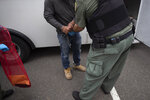In this July 8, 2019, photo, a U.S. Immigration and Customs Enforcement (ICE) officers transfer a man in handcuffs and ankle cuffs onto a van during an operation in Escondido, Calif. The carefully orchestrated arrest last week in this San Diego suburb illustrates how President Donald Trump's pledge to start deporting millions of people in the country illegally is virtually impossible with ICE's budget and its method of picking people up. (AP Photo/Gregory Bull)