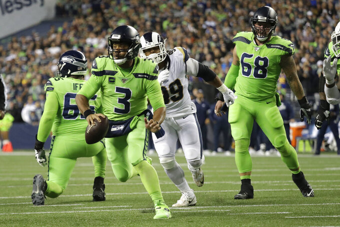 Seattle Seahawks quarterback Russell Wilson (3) scrambles before making a short pass to running back Chris Carson for a touchdown against the Los Angeles Rams during the second half of an NFL football game Thursday, Oct. 3, 2019, in Seattle. (AP Photo/Elaine Thompson)