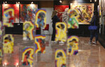 Indonesian women wearing face masks to help curb the spread of the coronavirus visit an art exhibition from Indonesian artists response to the pandemic in Jakarta, Indonesia, Thursday, Oct. 15, 2020. (AP Photo/Achmad Ibrahim)