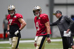 New Orleans Saints quarterbacks Drew Brees (9) and Taysom Hill (7) go through drills in front of offensive coordinator Pete Carmichael during practice at their NFL football training facility in Metairie, La., Monday, Aug. 24, 2020. (AP Photo/Gerald Herbert, Pool)