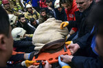 A person extrapolated from the debris is carried on a stretcher by rescuers after a eight-story building collapsed in Istanbul, Wednesday, Feb. 6, 2019.  An eight-story building collapsed in Istanbul on Wednesday, killing at least one person and trapping several others inside the rubble, Turkish media reports said. (DHA via AP)