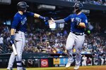 Seattle Mariners' Ty France, right, celebrates with teammate Jarred Kelenic, left, after scoring a run against the Arizona Diamondbacks during the fourth inning of a baseball game Sunday, Sept. 5, 2021, in Phoenix. (AP Photo/Ross D. Franklin)