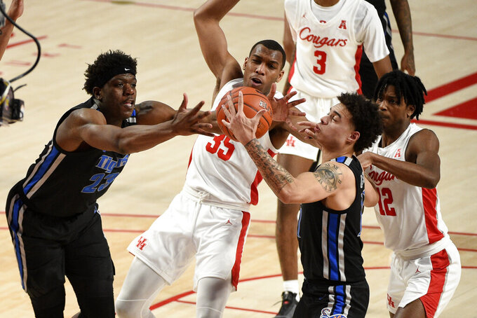 Memphis center Malcolm Dandridge (23), Houston forward Fabian White Jr. (35), Memphis guard Lester Quinones, second from right, and Houston guard Tramon Mark (12) vie for a rebound during the first half of an NCAA college basketball game, Sunday, March 7, 2021, in Houston. (AP Photo/Eric Christian Smith)