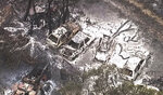 FILE - In this Nov. 27, 2018, file image made from aerial video, burned buildings and vehicles are seen on a scorched landscape after a wildfire in the Deepwater area of Queensland state in Australia. The Labor Party has pledged to achieve zero greenhouse gas emissions by 2050, an ambitious target the conservative government says would wreck Australia's economy. Labor says failing to act on climate change would also cost the economy. (Pool Photo via AP, File)
