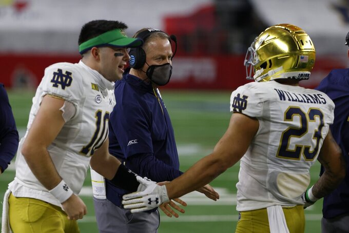 Notre Dame quarterback Drew Pyne (10) and head coach Brian Kelly, center, congratulate running back Kyren Williams (23) on his touchdown run in the first half of the Rose Bowl NCAA college football game against Alabama in Arlington, Texas, Friday, Jan. 1, 2021. (AP Photo/Ron Jenkins)