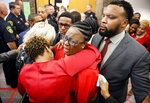 Botham Jean's mother, Allison Jean, center, escorted by civil rights attorney Lee Merritt, right,, is hugged by family members outside the courtroom after fired Dallas police officer Amber Guyger was found guilty of murder, Tuesday, Oct. 1, 2019, in Dallas. Guyger shot and killed Botham Jean, an unarmed 26-year-old neighbor in his own apartment last year. She told police she thought his apartment was her own and that he was an intruder. (Tom Fox/The Dallas Morning News via AP, Pool)