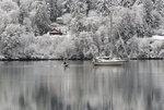 A dinghy motors toward a sailboat anchored in Liberty Bay in Poulsbo, Wash., on a snowy Monday, Jan. 13, 2020. (Meegan M. Reid/Kitsap Sun via AP)