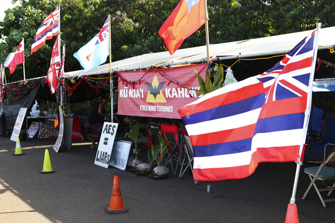 This Oct. 30, 2019, photo shows flags adorning an encampment on the side of a highway where protesters are fighting against the construction of eight wind turbines in Kahuku, Hawaii. The ongoing protest by mostly Native Hawaiians stalling construction of a $1.4-billion telescope on the Big Island has inspired protests on Oahu, the state's most populous island, with efforts to block the turbines and to stop the redevelopment of a beach park. (AP Photo/Jennifer Sinco Kelleher)