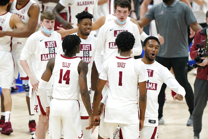 Alabama's Keon Ellis (14) and Herbert Jones (1) leave the court after Alabama beat Tennessee in an NCAA college basketball game in the Southeastern Conference Tournament Saturday, March 13, 2021, in Nashville, Tenn. (AP Photo/Mark Humphrey)