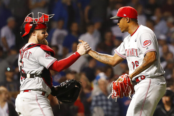 Cincinnati Reds catcher Tucker Barnhart and relief pitcher Raisel Iglesias celebrate the team's 4-2 win over the Chicago Cubs in a baseball game Tuesday, Sept. 17, 2019, in Chicago. (AP Photo/Charles Rex Arbogast)