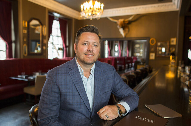 In this Feb. 11, 2020, photo, Brent Frederick, founder of Jester Concepts, a restaurant group in Minneapolis poses at P.S. Steak. Frederick puts a 3% voluntary surcharge on guest checks to help pay for health insurance and mental health services and says almost all guests agree to pay it. (AP Photo/Andy Clayton-King)