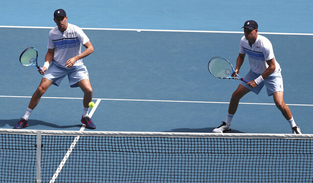 Mike Bryan, left, of the U.S. and his brother Bob play during their third round doubles match against Croatia's Ivan Dodig and Slovakia's Filip Polasek at the Australian Open tennis championship in Melbourne, Australia, Monday, Jan. 27, 2020. (AP Photo/Dita Alangkara)