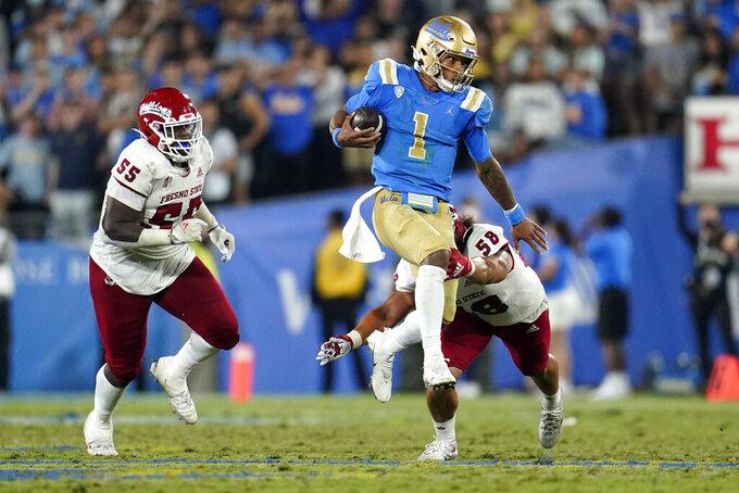 UCLA quarterback Dorian Thompson-Robinson (1) leaps between Fresno State defensive tackle Leonard Payne Jr. (55) and linebacker Tyson Maeva (58) during the second half of an NCAA college football game Sunday, Sept. 19, 2021, in Pasadena, Calif. (AP Photo/Marcio Jose Sanchez)