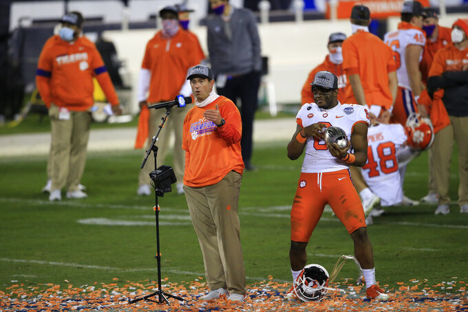 Clemson head coach Dabo Swinney addresses the media as Clemson linebacker Mike Jones Jr. (6) gestures behind him following their 34-10 victory over Notre Dame at the Atlantic Coast Conference championship NCAA college football game, Saturday, Dec. 19, 2020, in Charlotte, N.C. (AP Photo/Brian Blanco)