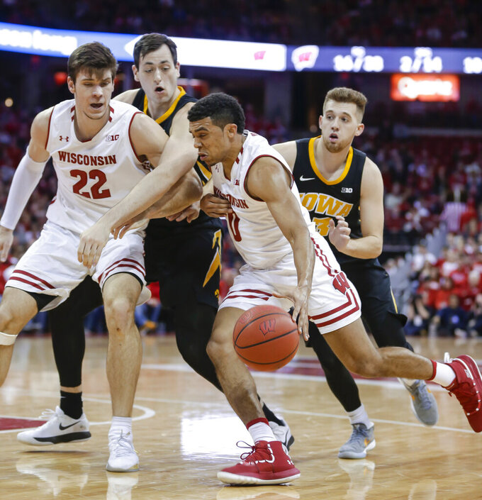 Wisconsin's D'Mitrik Trice (0) dribbles against Iowa's Ryan Kriener, behind, and Jordan Bohannon, right, as Wisconsin's Ethan Happ (22) blocks during the second half of an NCAA college basketball game Thursday, March 7, 2019, in Madison, Wis. Wisconsin won 65-45. (AP Photo/Andy Manis)