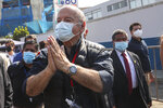 Avanza Pais party presidential candidate Hernando De Soto, wearing a mask to curb the spread of the new coronavirus, waves to supporter upon his arrival to vote during general elections in Lima, Peru, Sunday, April 11, 2021. (AP Photo/Martin Mejia)