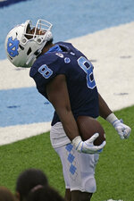 North Carolina running back Michael Carter (8) reacts following a touchdown run against Virginia Tech during the second half of an NCAA college football game in Chapel Hill, N.C., Saturday, Oct. 10, 2020. (AP Photo/Gerry Broome)