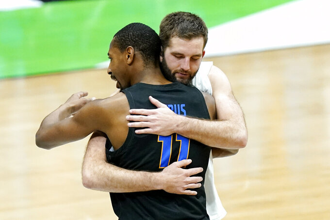 UC Santa Barbara's Brandon Cyrus (11) hugs Creighton's Mitch Ballock after a college basketball game in the first round of the NCAA tournament at Lucas Oil Stadium in Indianapolis Saturday, March 20, 2021. Creighton won 63-62. (AP Photo/Mark Humphrey)
