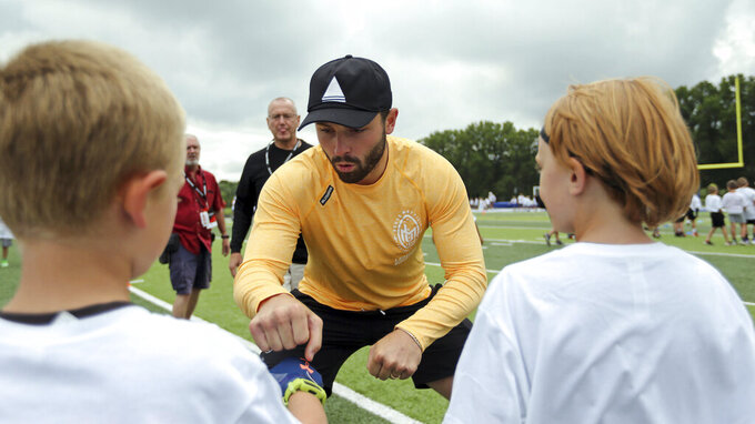 Cleveland Browns quarterback Baker Mayfield fist bumps with a participant at the Baker Mayfield ProCamp in Gates Mills, Ohio, Wednesday, July 21, 2021.(Joshua Gunter/Cleveland.com via AP)