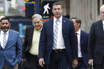 California Republican Rep. Duncan Hunter, center, walks towards federal court in front of his father, former Rep. Duncan L. Hunter, left, Tuesday, Dec. 3, 2019, in San Diego. Hunter said in a TV interview that aired Monday he plans to plead guilty to the misuse of campaign funds at a federal court hearing Tuesday in San Diego. (AP Photo/Gregory Bull)