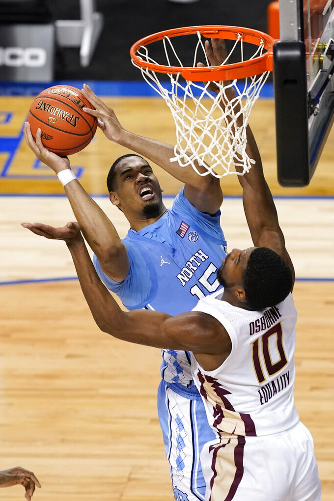 North Carolina forward Garrison Brooks (15) goes up for a shot as Florida State forward Malik Osborne (10) defends during the second half of an NCAA college basketball game in the semifinal round of the Atlantic Coast Conference tournament in Greensboro, N.C., Friday, March 12, 2021. (AP Photo/Gerry Broome)