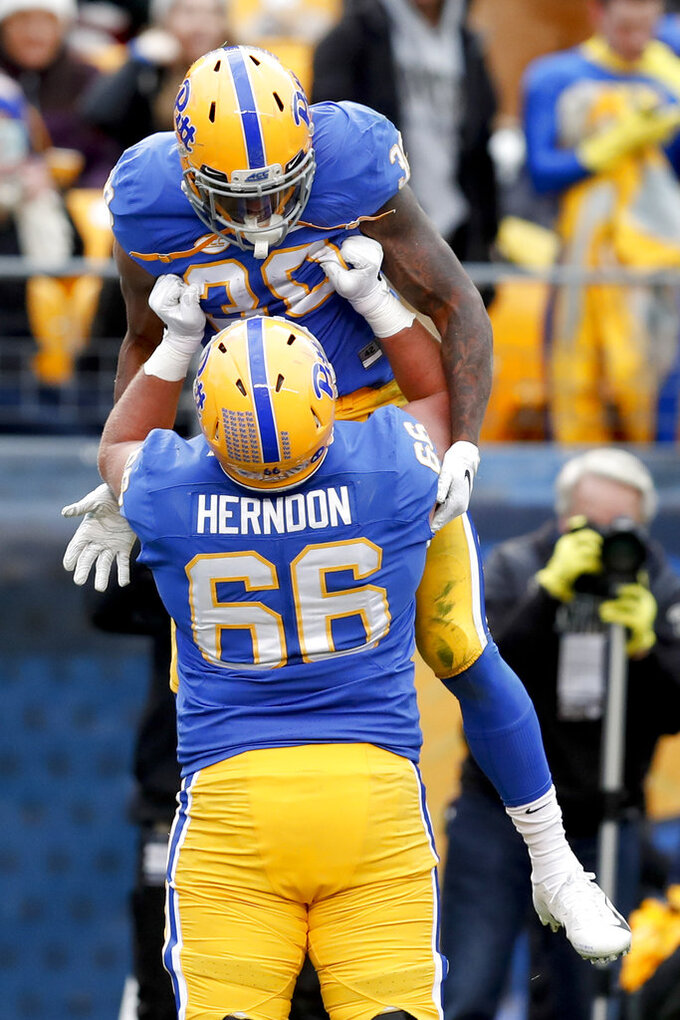 Pittsburgh running back Qadree Ollison (30) is hoisted by offensive lineman Mike Herndon (66) after scoring a touchdown against Virginia Tech in the first quarter of an NCAA football game, Saturday, Nov. 10, 2018, in Pittsburgh. (AP Photo/Keith Srakocic)